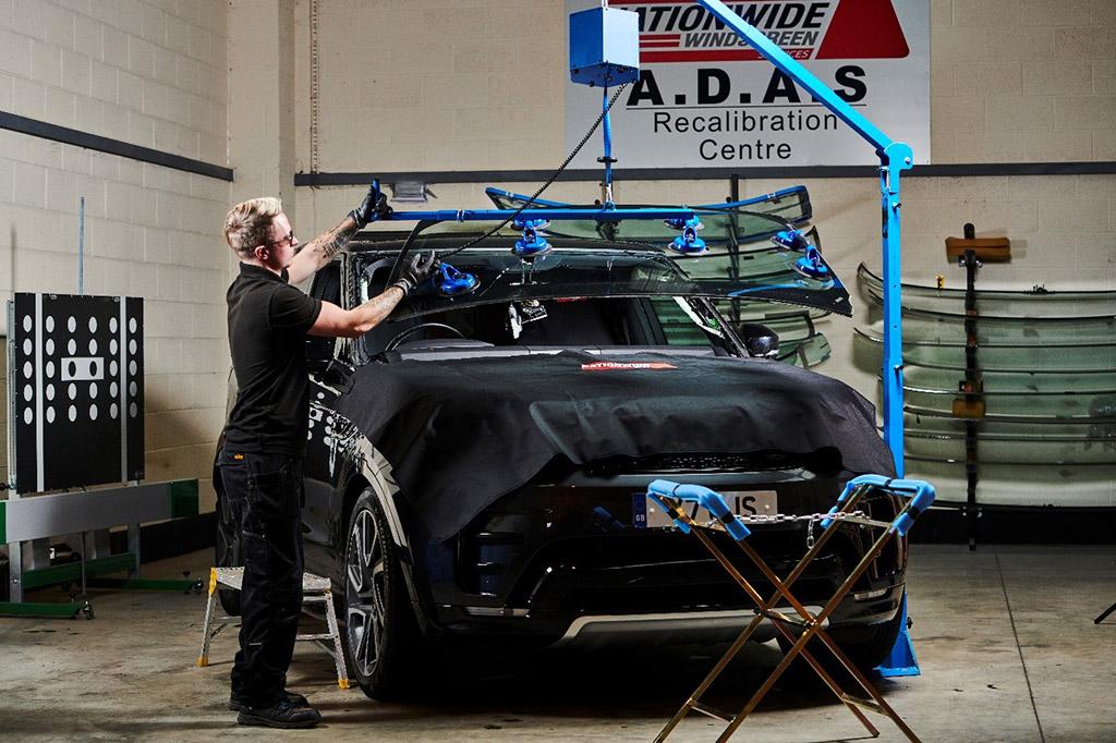 Technician replacing a car windscreen